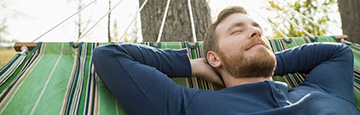 Young man relaxing on hammock, with hands behind his head
